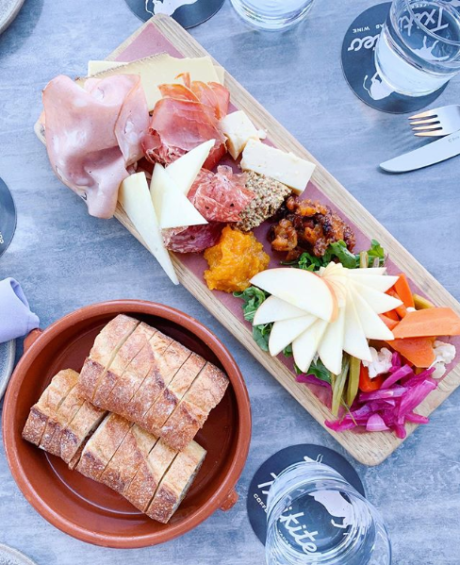 Photo of Txikiteo Charcuterie combo board with meat and cheese, pickled vegetables, mustards,  and bread from Acme Bakeshop taken from looking directly down at the table.