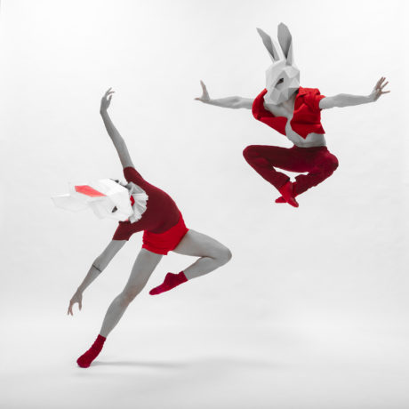 Ballet Dancers in paper, geometric bunny masks and red clothing.