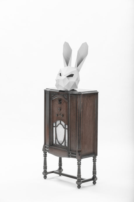 geometric paper white bunny mask sitting on top of an old wooden music player