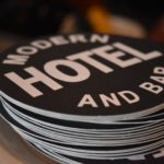 Stack of coasters in Boise, Idaho, branded with the modern bar and hotel logo, a black circle with white lettering.