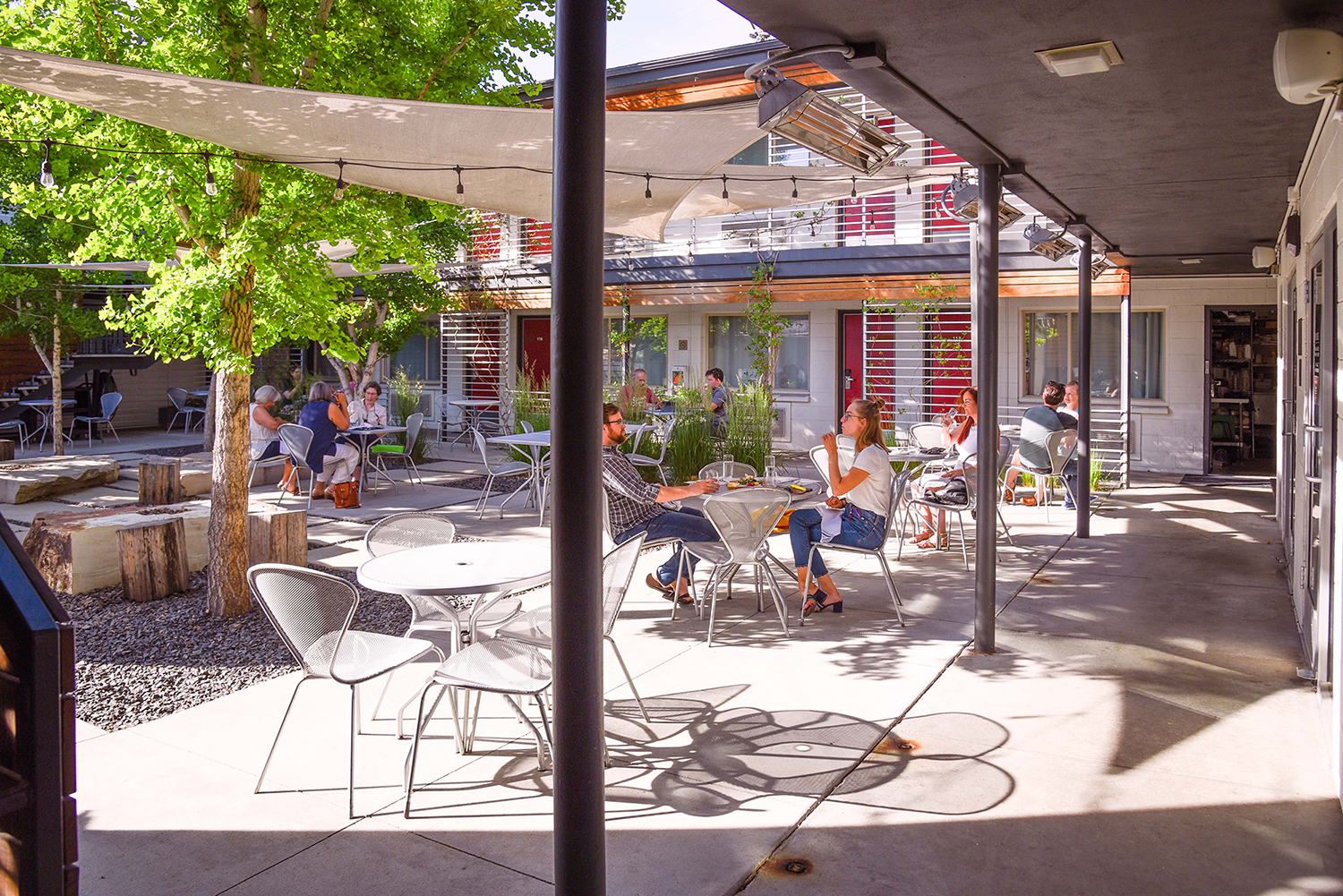 View of the Modern Hotel and Bar courtyard from the southeast corner of the patio. Several metal mesh tables with matching cherner-like chairs are occupied by patrons enjoying craft cocktails and appetizers. Reddish-orange hotel room doors are visible surrounding the courtyard. Ginkgo trees and sails provide shade.